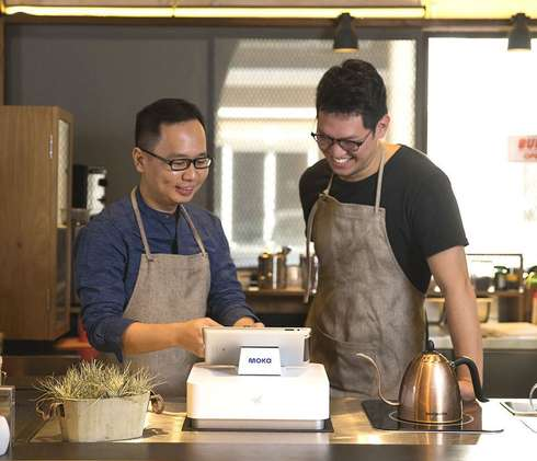 A coffee shop business owner who is instructing his employee (cashier man) to operate Moka POS as a more efficient cashier