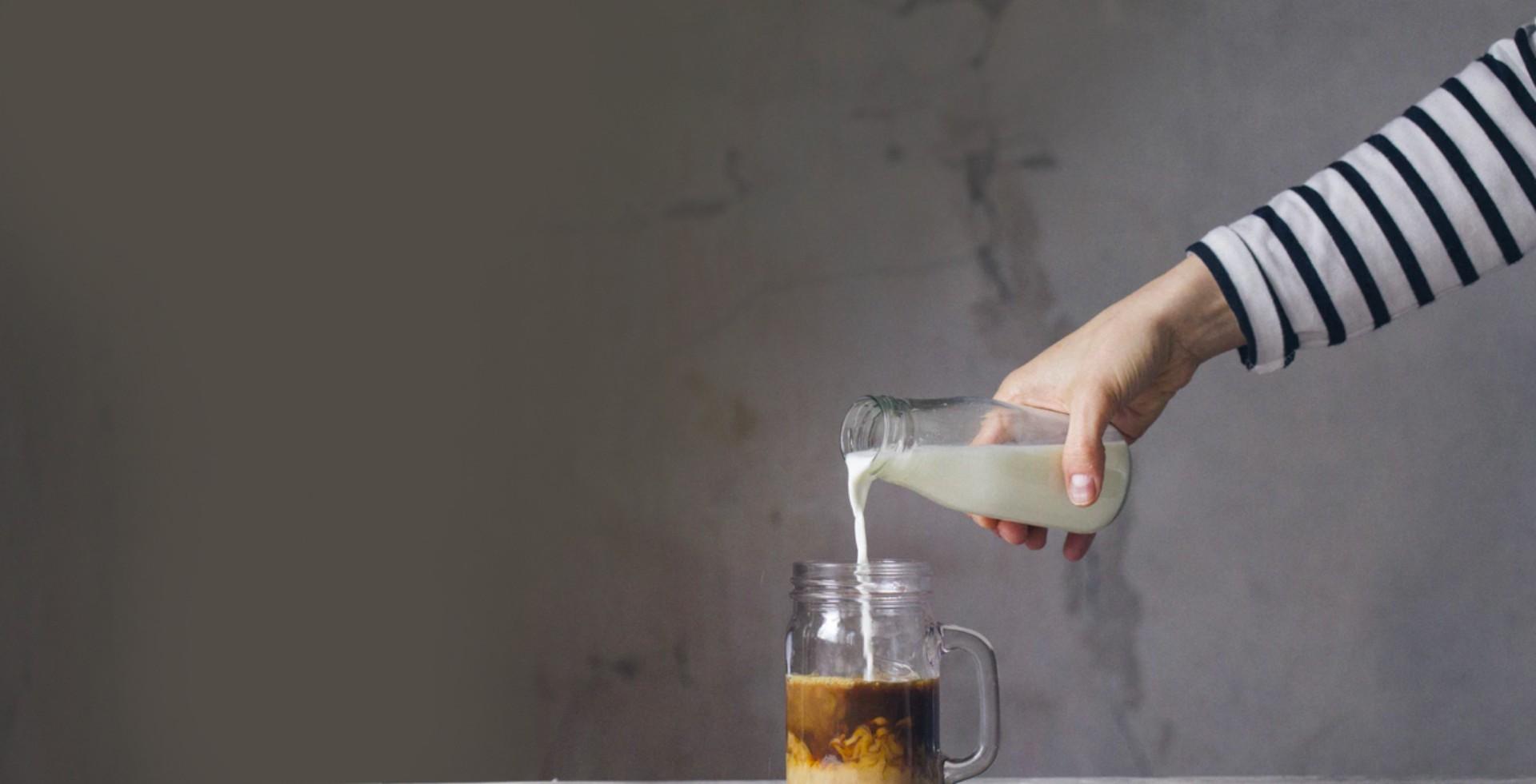 Pelayan yang menuangkan susu ke dalam gelas kopi espresso di suatu kafe modern dan minimalis di Jakarta Selatan