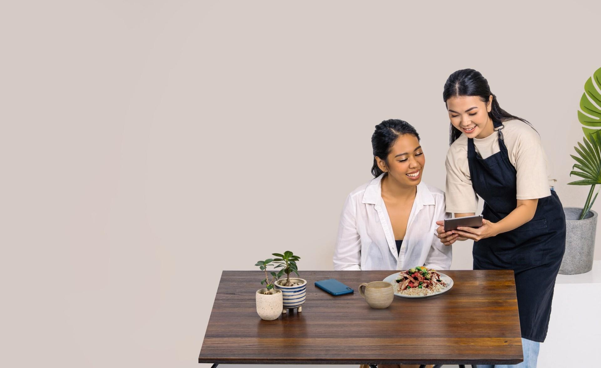 Pelayan di sebuah restoran cepat saji yang sedang menunjukkan aplikasi Moka ke pelanggan yang ingin membayar tagihan terpisah