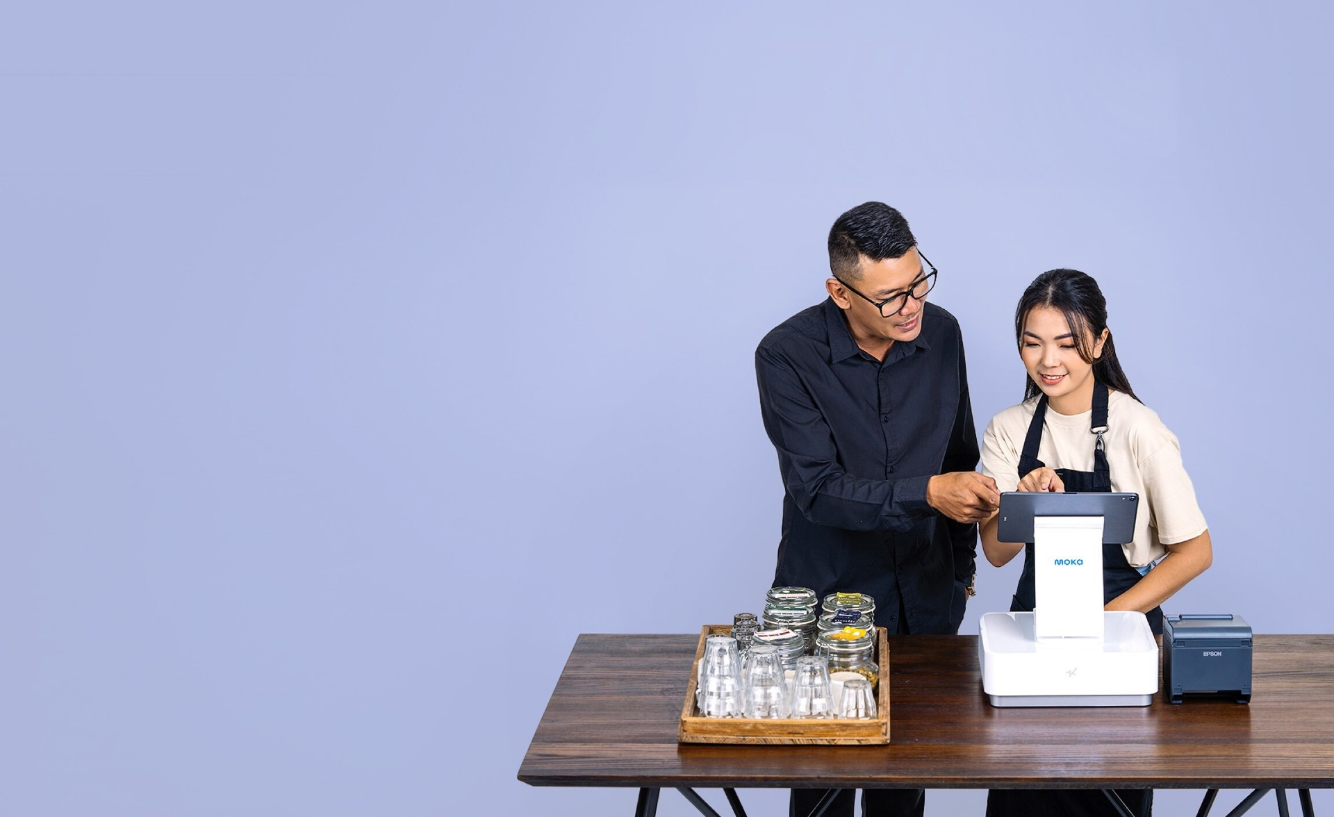 Pemilik bisnis toko kopi yang sedang memberi arahan karyawan untuk mengoperasikan Moka POS sebagai kasir yang lebih efisien