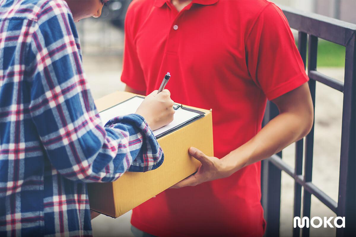 Seorang pelanggan sedang menerima paket yang dibelinya secara daring dari jasa pengiriman barang pilihannya